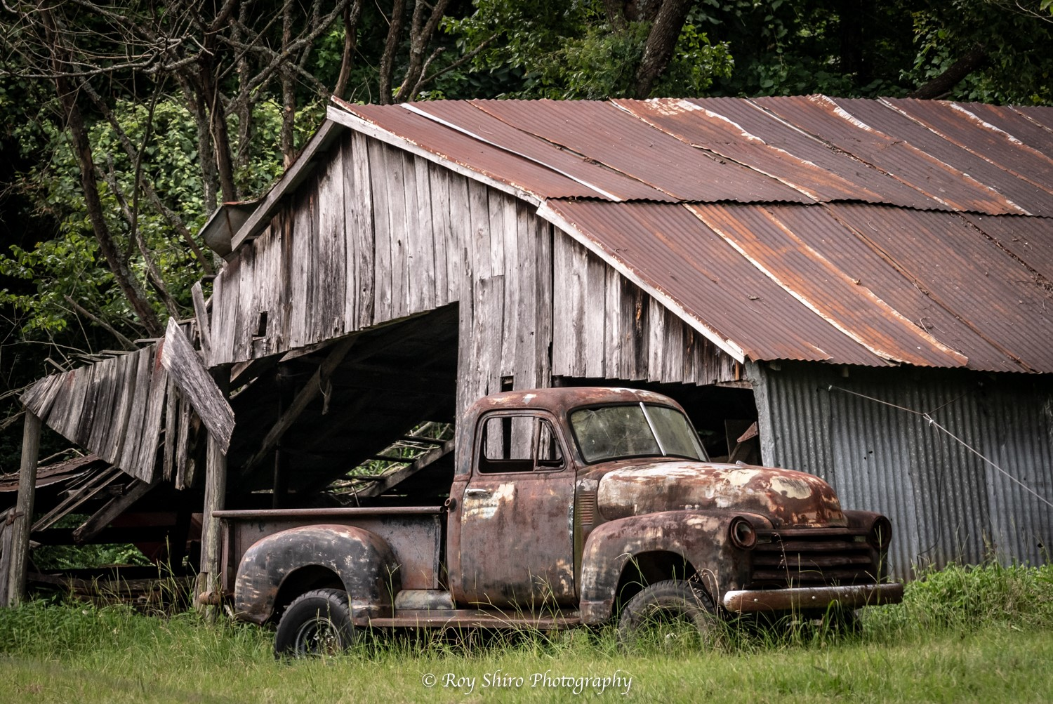 Rustic barn and rusty antique truck in a green pasture