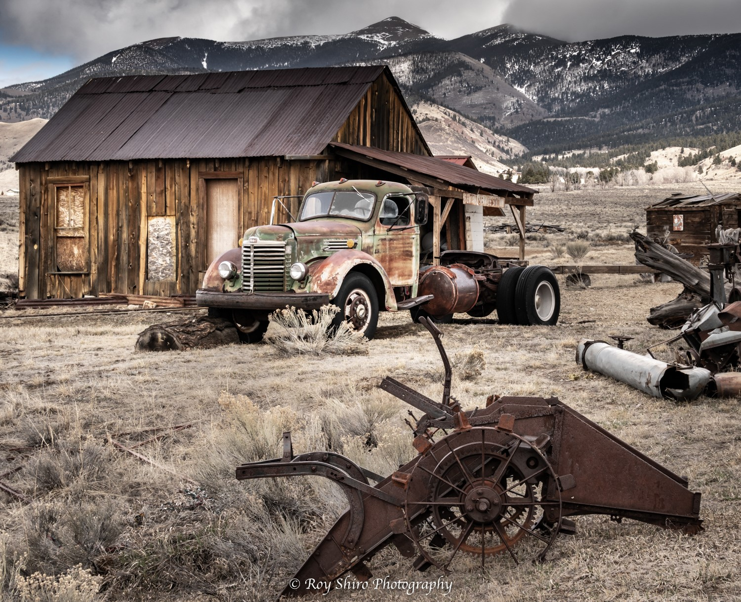 Rustic truck in front of a rustic cabin with a mountain range in the background